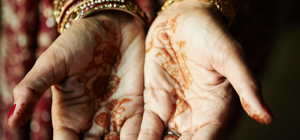 Bride's hands with traditional Indian Mehndi decorations or henna tattoos