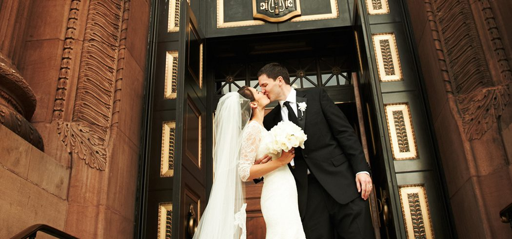 Bride and Groom kiss outside church at wedding in Philadelphia, PA - Event Planner