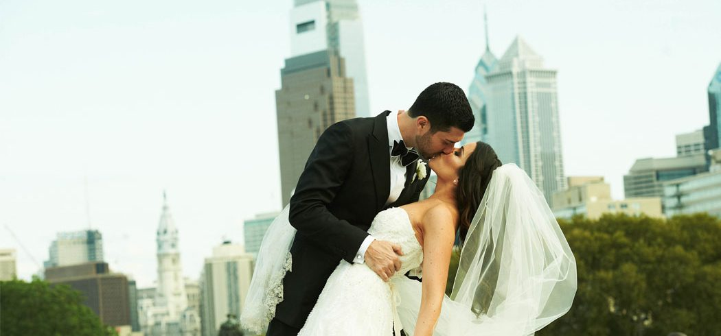Groom dips Bride and kissed during outside wedding portraits in Philadelphia, PA - Event Planner
