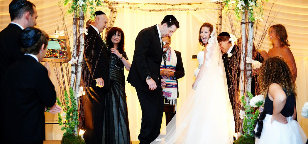 Bride and Groom laugh during Jewish wedding ceremony in Philadelphia, PA - Event Planner