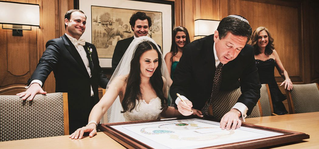 Bride and Groom sign document surrounded by friends in Philadelphia, PA - Event Planner